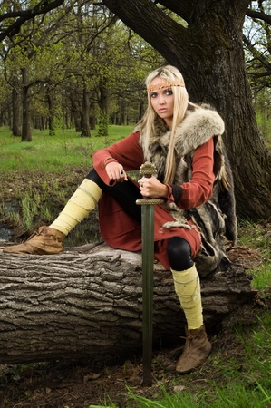 Viking girl warrior with sword in a wood 스톡 콘텐츠