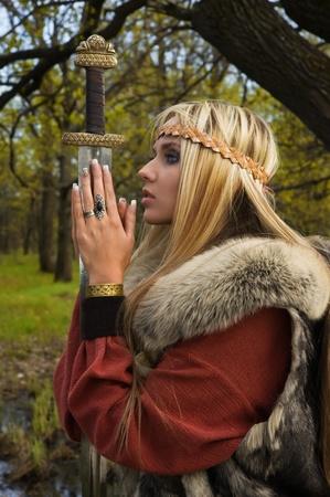 Viking girl warrior with sword in a wood Standard-Bild