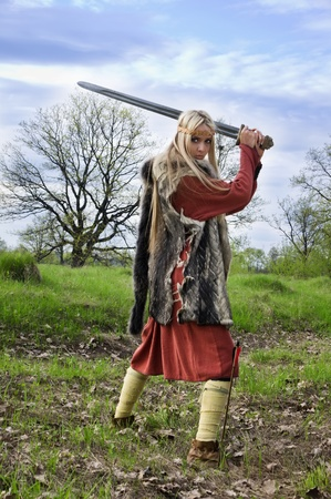 Viking girl warrior with sword in a fight Stock Photo
