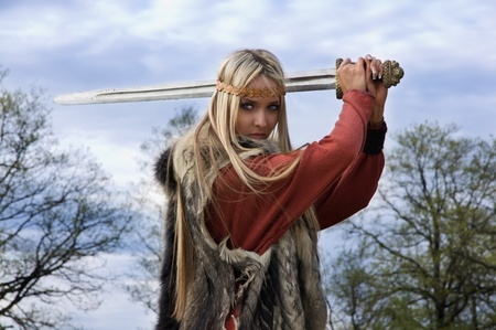 Viking girl warrior with sword fighted photo
