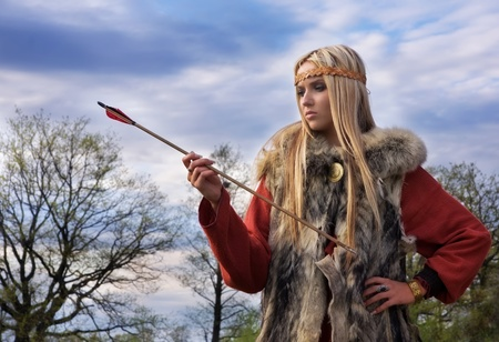 Viking girl warr with the arrow on a sky backround Stock Photo - 9780710