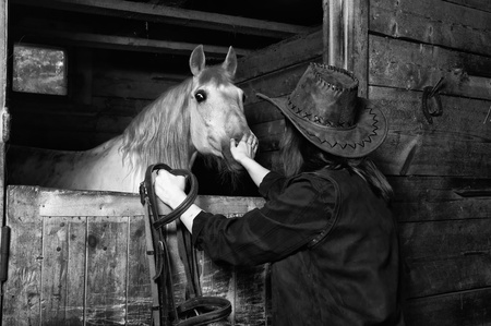 Young cowgirl in the stables at the ranch photo