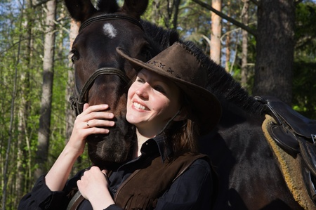 Happy cowgirl in hat hugging her horse photo
