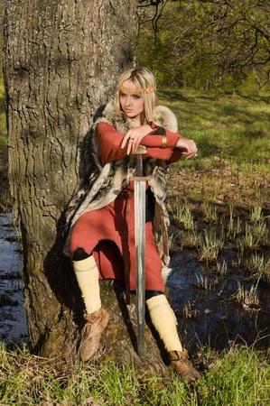 scandinavian girl: Portrait of the blonde girl in the Scandinavian suit with sword Stock Photo