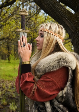 Viking girl warrior with sword in a wood photo