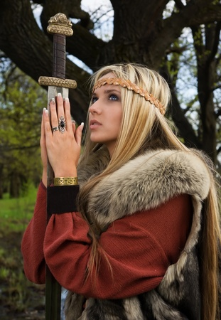 Viking girl warrior with sword in a wood Stock Photo