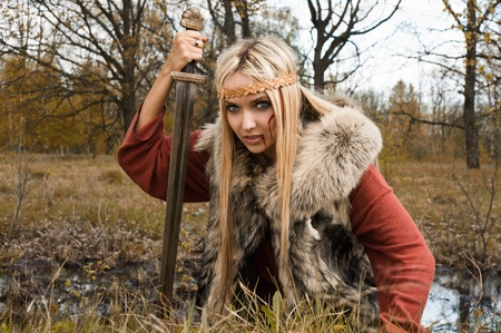 Viking girl warrior with sword in a fight photo