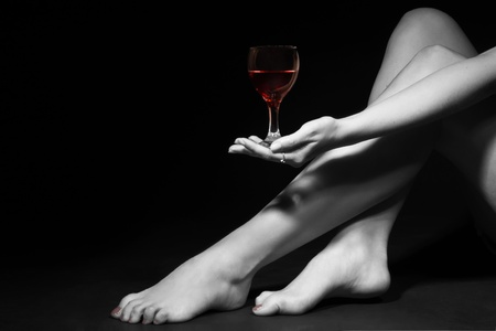 Beautiful girl legs and a glass of alcoholic beverage, black white photo (red wine in glass)    photo