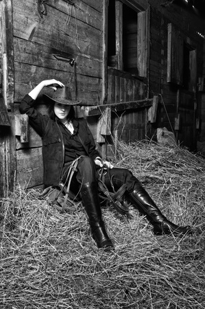 cute young farm girl: Young cowgirl sitting on hay in the stable