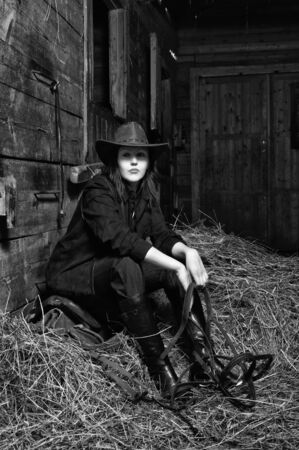 Young cowgirl sitting on hay in the stable photo