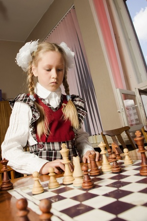Little girl playing chess at a table photo
