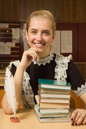 Portrait of happy school girl at her desk Stock Photo - 9780867