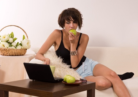 Beautiful young woman relaxing on sofa with laptop and apple Stock Photo - 9904032