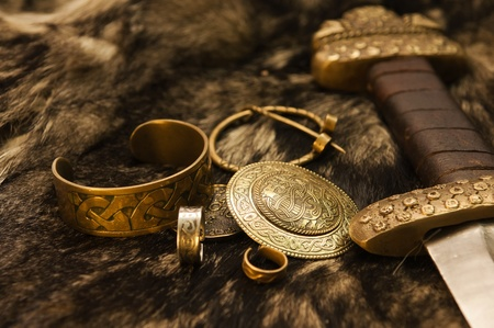 Stilleven met oude scandinavische juwelen en zwaard op een bont Stockfoto
