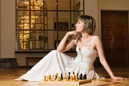 Young  blond woman play chess in the rich interior photo