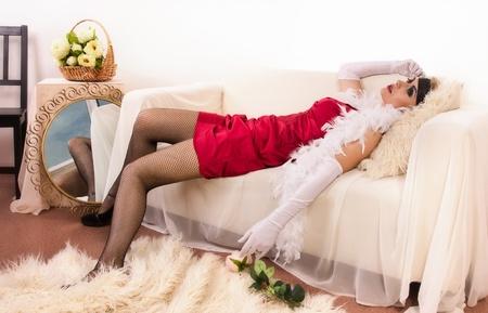 Crime scene in a retro style. Lifeless  woman lying on the sofa Stock Photo