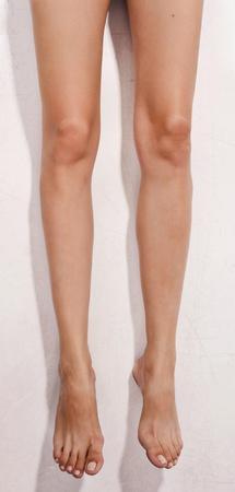 Barefoot woman legs on a wall backgrund  photo