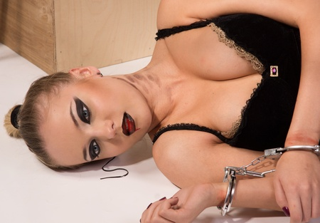 handcuffs female: Crime scene simulation: dead blonde in the handcuffs lying on the floor Stock Photo