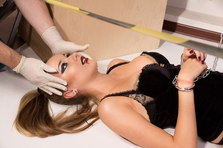 female prisoner: Forensic expert collecting evidence in a crime scene (imitation) Stock Photo