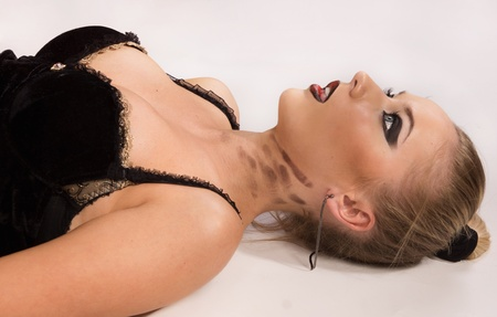 Crime scene simulation: pretty blonde in the handcuffs lying on the floor Stock Photo