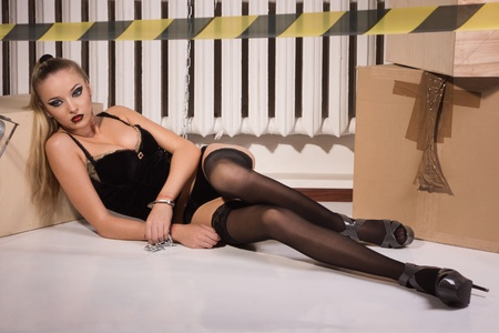slave girl: Crime scene simulation: dead blonde in the handcuffs lying on the floor Stock Photo