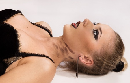 slave girl: Crime scene simulation: pretty blonde in the handcuffs lying on the floor Stock Photo