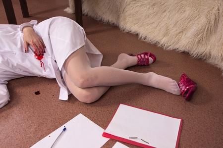 assassination: Crime scene simulation: dead nurse lying on the floor Stock Photo