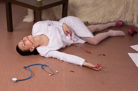 homicide: Crime scene simulation: dead nurse lying on the floor Stock Photo
