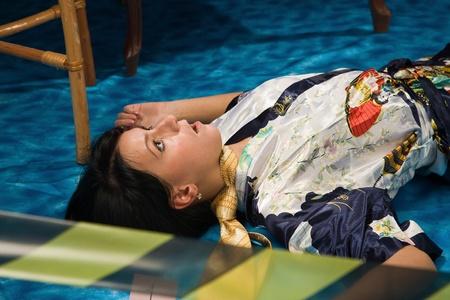 assassination: Crime scene simulation: strangled  brunette lying on the floor