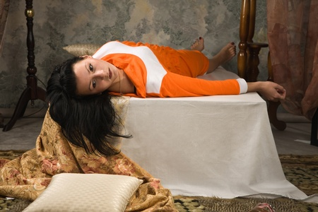 Crime scene simulation: lifeless  brunette lying on the bed photo