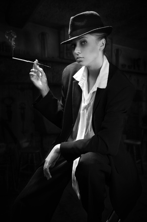 Vintage portrait of the adult woman smoking cigarette in bar photo