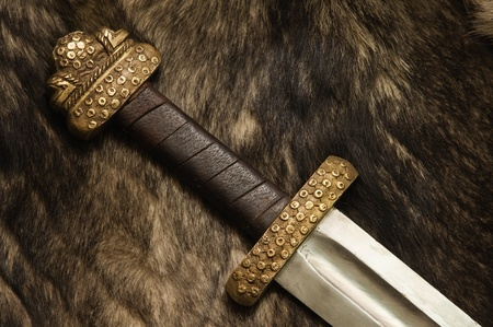 Still life with ancient scandinavian sword on a fur photo