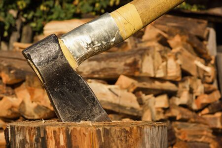 Axe in log on a firewoods background   photo
