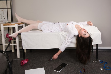 Crime scene imitation. Nurse lying on the sofa