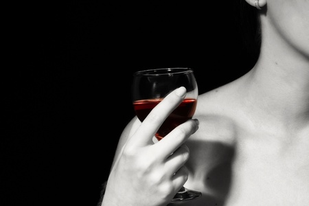 finger to lips: Glass with a red wine in a female hand