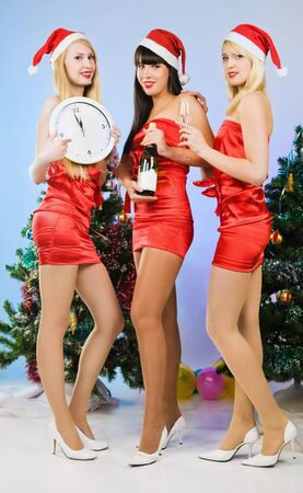 Three pretty sexy girls wearing santa claus clothes with a shampagne photo