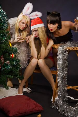 Christmas party. Three pretty sexy girls wearing santa claus photo