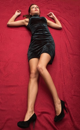 Crime scene simulation: dead  brunette lying on the floor photo
