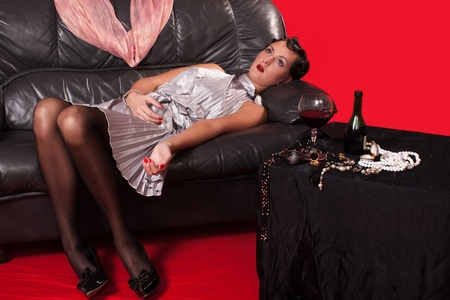 Crime scene in a retro style. Lifeless woman lying on the sofa photo