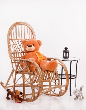 Old wooden rocking chair with toys over white background photo