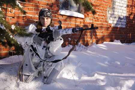Sniper girl in white camouflage aiming with rifle at winter forest. photo