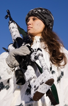 camouflage woman: Sniper girl in white camouflage aiming with rifle on a blue sky background