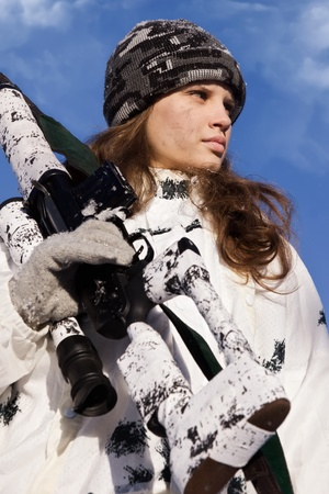Sniper girl in white camouflage aiming with rifle on a blue sky background photo