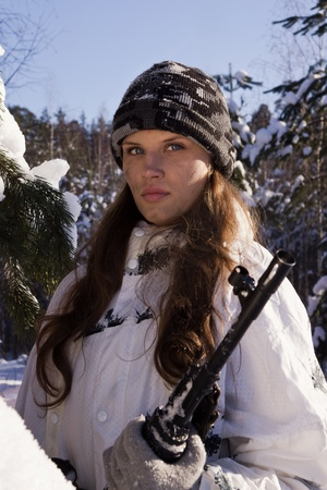 Sniper girl in white camouflage aiming with rifle at winter forest  photo