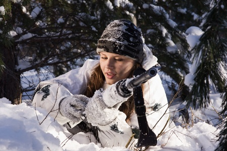 Sniper girl in white camouflage aiming with rifle at winter forest. Stock Photo - 12896231