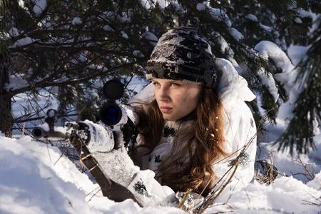 snajper: Dziewczyna w białym kamuflażu Sniper celu z karabinem w zimowym lesie.