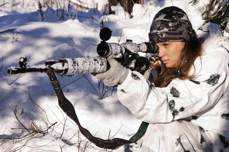 mujer con arma: Niña de francotirador en el camuflaje blanco apuntando con el rifle en el bosque de invierno.