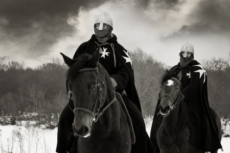 Medieval knights of St. John (Hospitallers) riding on a bay horses
