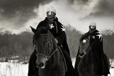 Mittelalterliche Ritter von St. John (Johanniter) reitet auf einem braunen Pferden Standard-Bild - 13362790