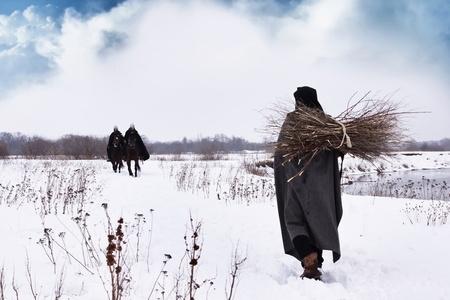 Middeleeuwse boer met een bundel brandhout en paardrijden ridders hospitaalridders Stockfoto